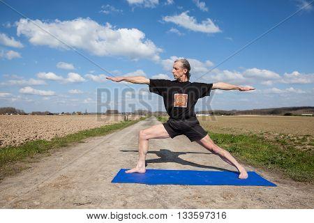 on an sunny day this man enjoys Virabhadrasana yoga in nature
