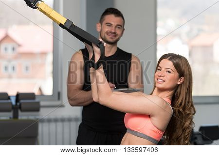 Gym Coach Helping Woman On Trx Fitness Straps