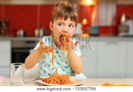 Adorable little girl eating spaghetti at table