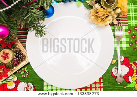 New Year Christmas tablecloth with a pattern of Santa Claus HOLLY gifts a fork with a plate and golden candlestick with flower