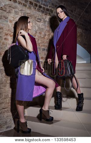 fashion shot of beautiful girls of models in lingerie with shopping bags and colored coats in the studio with a hard light