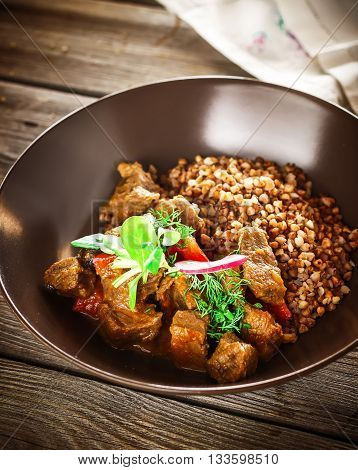 Buckwheat with meat and greens. Dark wooden background. Selective focus.