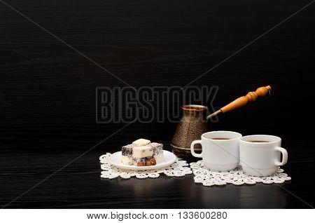 Rahat lokum and two cups of coffee on white napkins pots on a black background. Space for text
