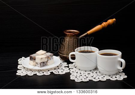 Coffee for two Turkish Delight and Cezve on a black background