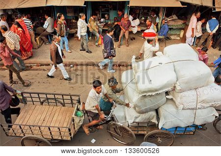 KOLKATA, INDIA - JAN 20, 2016: Crowd of people on narrow street with marketplaces stores and cargo workers on January 20, 2016 in Calcutta. Kolkata has a density of 814.80 vehicles per km road length