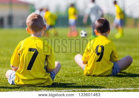 Young football team wearing sports yellow soccer dress. Soccer players on sports field. Football soccer match for children. Youth sports team sitting together and watching football soccer game. team work