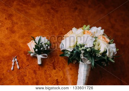 Bride's earrings, cute boutonniere and bridal bouquet on rustic wooden background.