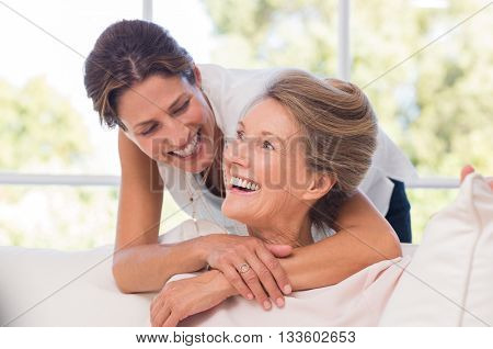 Portrait of mother and daughter hugging. Happy senior mother and adult daughter embracing at home. Cheerful woman embraces older woman and looking at each other.