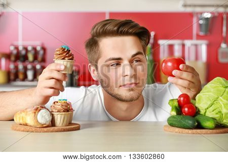 Man with healthy and unhealthy food in kitchen