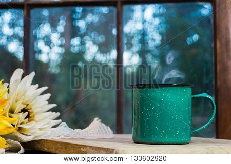 Old green stoneware mug with window view in background