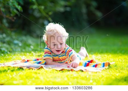 Kids reading a book in summer garden. Little boy playing in school yard. Preschool kid playing and learning. Student doing homework. Kindergarten children study and read books.