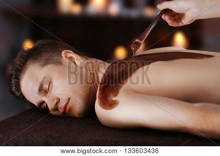 Man having cosmetic mask in spa salon