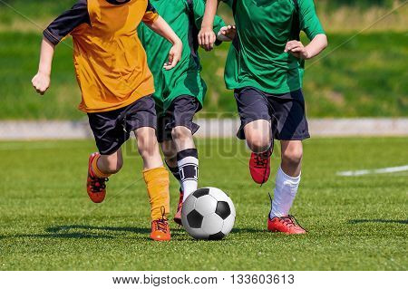Young boys playing football soccer game on sports field. Running players in colorful green and yellow uniforms. Kids running and kicking soccer ball