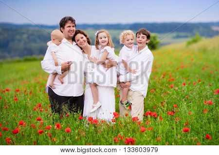 Big happy family with four children in red poppy flower field. Mother father toddler boy and girl teenager son and little baby walking in summer meadow picking poppies. Kids pick flowers.