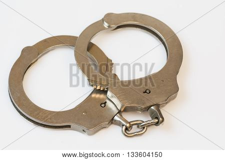 Silver metal hinged handcuffs on white with chain