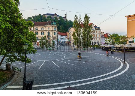 LJUBLJANA SLOVENIA - 27TH MAY 2016: A view towards Town Square Ljubljana Castle and Triple bridges during the morning from Preseren Square. Buildings and people can be seen.