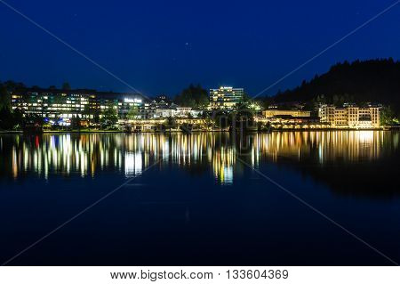 BLED SLOVENIA - 27TH MAY 2016: A view of buildings from across Bled Lake at night. Reflections can be seen in the water.