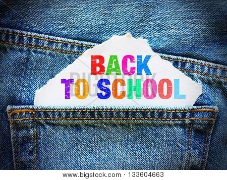 Back to school on white paper in the pocket of blue denim jeans