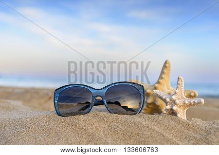 Marine still life. Flip flops, sunglasses and starfish on sea and sky background.