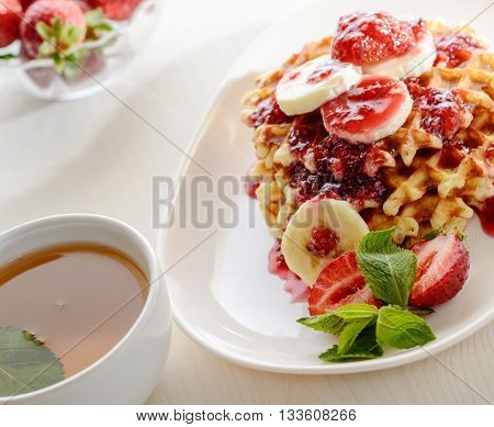 waffles dessert with strawberries bananas and mint. Cup of tee for healthy breakfast