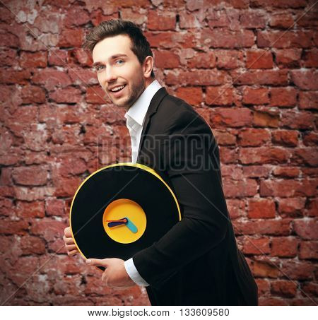 Man in black suit holding big clock is late for work on brick background