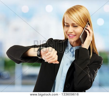 Businesswoman looking at wrist watch on blurred background
