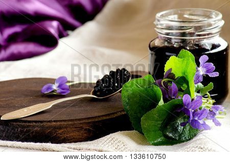 The elderberry jam in an open jar a spoon and a bouquet of violets on the table