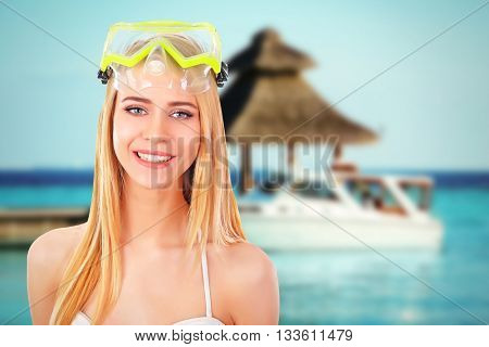 Young beautiful woman in swimsuit and diving mask on blurred resort background