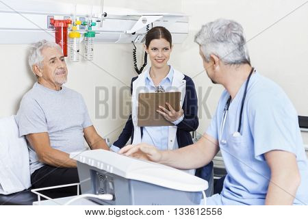 Physiotherapist And Patient Looking At Doctor In Rehab Center