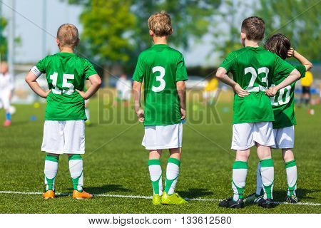Group Of Children In Soccer Team Having Training and Watching Soccer Match. Group of Boys Soccer Players Standing Together and Supporting Team