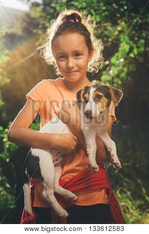 girl holding a small dog breed Jack Russell Terrier smiles and looks at the camera on a summer day