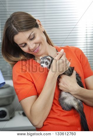 Woman Looking At Weasel In Veterinary