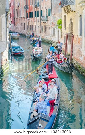 Venice Italy - Jun 11 2014: Traditional Venetian Gondola Sailing Tourists In Remote Canal In Venice