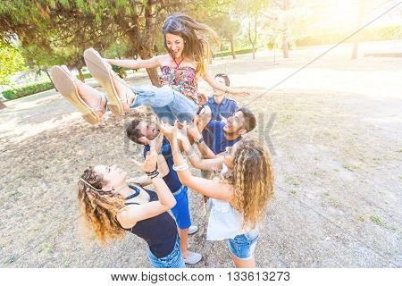 Group Of Friends Throwing A Woman In The Air