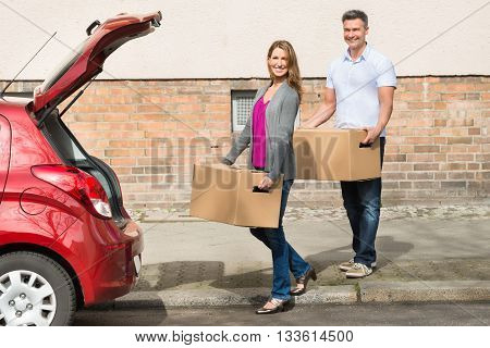 Mature Happy Couple Carrying Box For Putting In Car