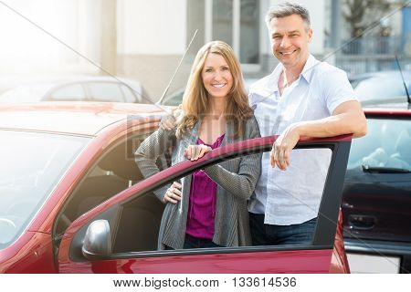Portrait Of Happy Couple Standing With Their Newly Purchased Red Car