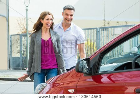 Overjoyed Happy Mature Couple Standing In Front Of New Car