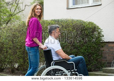 Portrait Of Happy Woman With Her Disabled Husband O9n Wheelchair