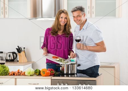 Wife Preparing Food While Her Husband Holding Glass Of Wine In Kitchen