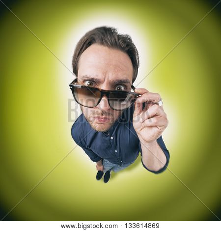 Funny man looking through his eye wear with opened eyes