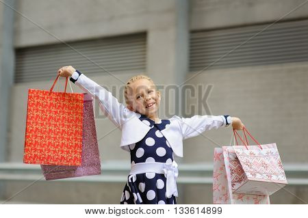 Happy little girl with shopping bags. Cute little girl on shopping. Portrait of a kid with shopping bags. Child in dress, near shopping mall having fun.