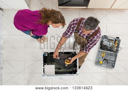 High Angle View Of Woman Looking At Technician Checking Washing Machine With Digital Multimeter