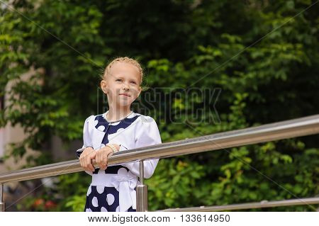 Portrait of a little girl. Child in a beautiful dress looking to side, hands on railing. Green tree in background.