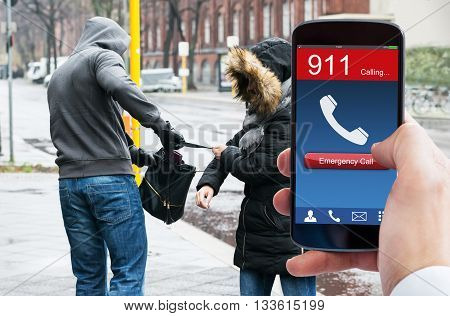 Person's Hand Dialing Emergency Call On Mobile Phone While Burglar Stealing Handbag From Woman
