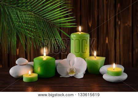 Spa stones with burning candles and flowers on wooden background