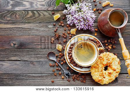 Rustic wooden background with cup and cezve of coffee peanut tart and lilac flowers. White vintage dinnerware and spoon. Breakfast at summer morning. Top view place for text.