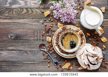 Rustic wooden background with cup of coffee milk meringue cinnamon and lilac flowers. White vintage dinnerware and spoon. Breakfast at summer morning. Top view place for text.