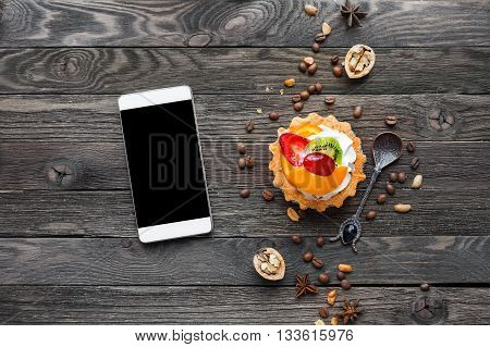 Wooden rustic background with fruit tart and spices - peanuts anise stars coffee beans walnuts. Tasty dessert with strawberry kiwi orange peach and whipped cream. Smartphone good for mock up.