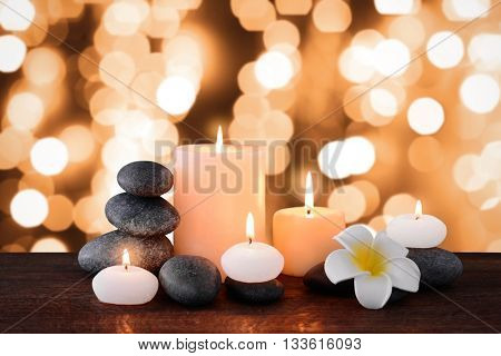 Spa stones with burning candles and flowers on festive background