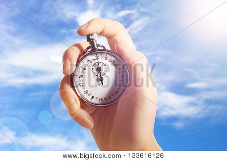 Woman holding stopwatch against blue sky. Concept of time